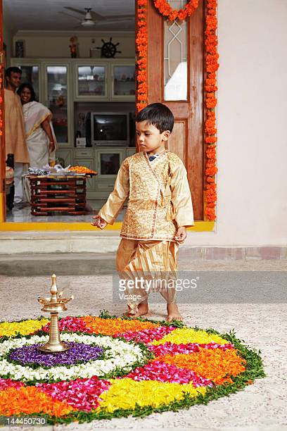 Child standing next to floral decoration