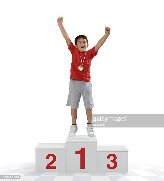 Child standing on a place podium in first place cheering