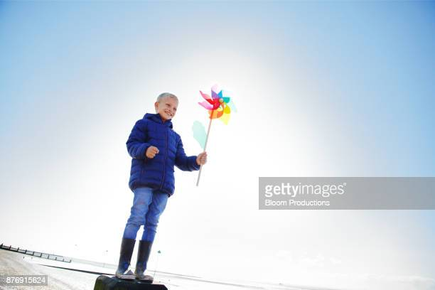 Child standing on a post at the beach holding a windmill
