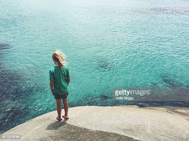Child standing on a rock looking at the ocean