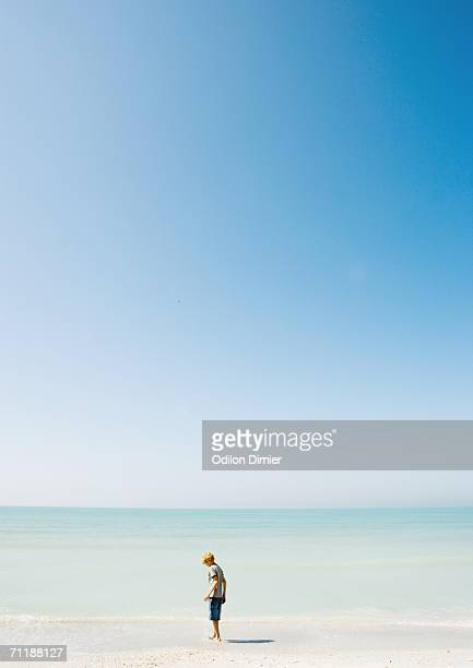 Child standing on beach in mid-distance