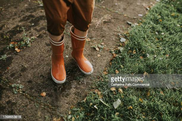 child standing on paved area in bright orange wellies - legs apart stock pictures, royalty-free photos & images