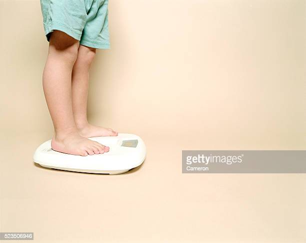 child standing on scale - cameron young stock photos and pictures