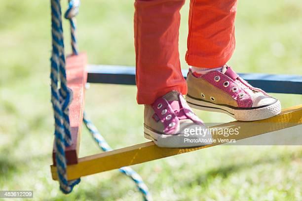 child standing on swing, low section - ジャングルジム ストックフォトと画像