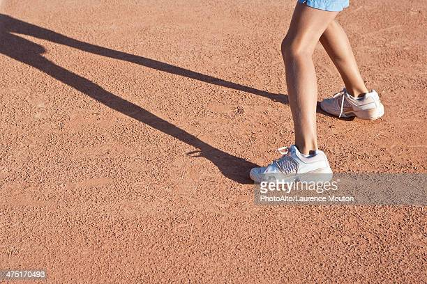 Child standing on tennis court, low section