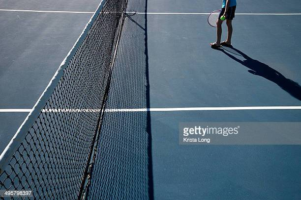Child standing on tennis court with a long shadow.