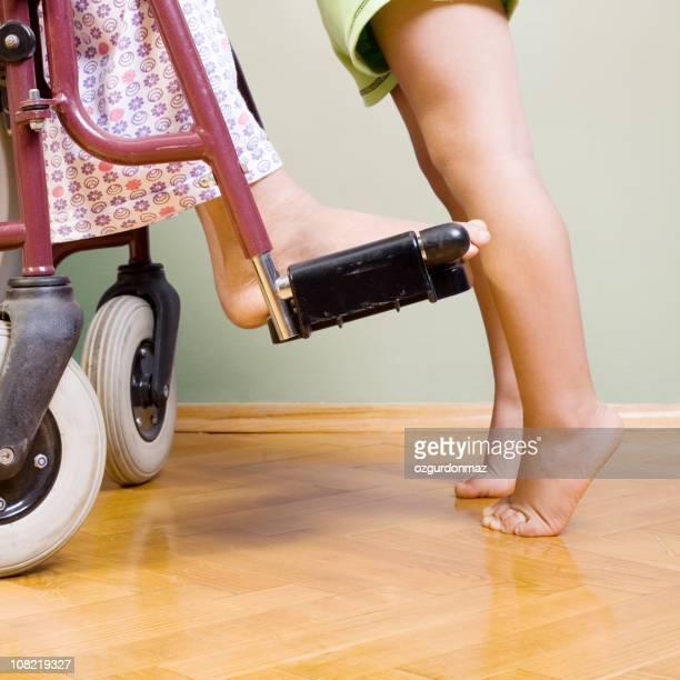 Enfant sur la pointe des pieds, debout sur le devant en fauteuil roulant
