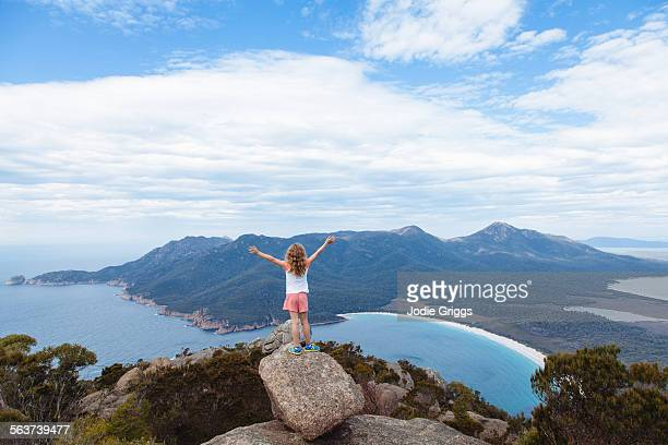 Child standing on top of mountain with arms in air