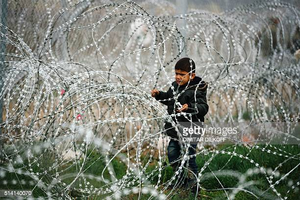 TOPSHOT A child stands among a razortopped fence close to the gate at the GreekMacedonian border near the Greek village of Idomeni on March 7 where...