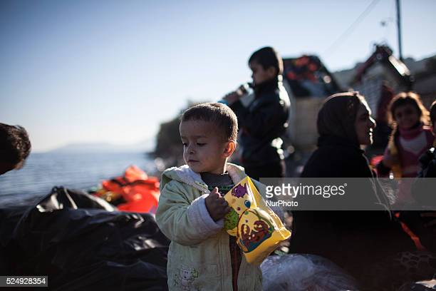 A child stands as refugees and migrants riding a dinghy reach the shores of the Greek island of Lesbos after crossing the Aegean Sea from Turkey on...