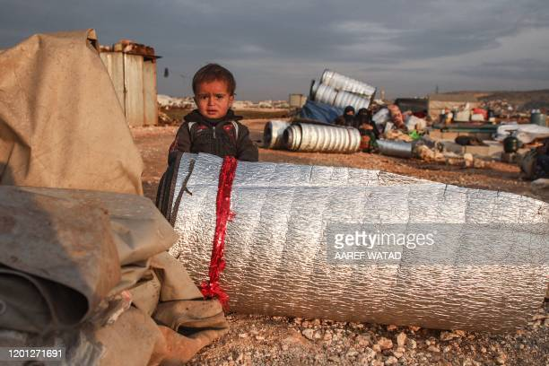 Child stands behind rolled-up thermal insulation foil out in the open at a camp for displaced Syrians east of Sarmada in the north of the...