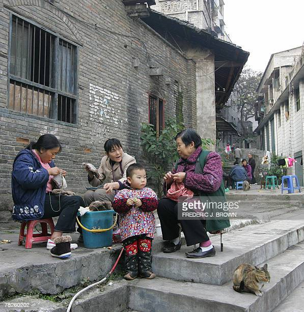 A child stands close to women doing their chores in old Wanzhou formerly known as Wanxian the largest city between Chongqing and Yichang downstream...