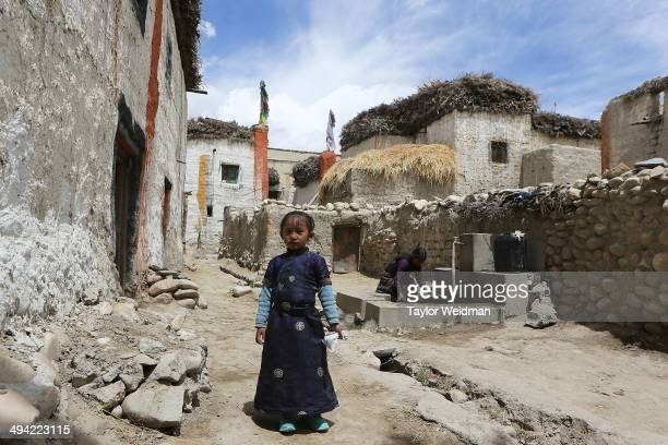 A child stands for a portrait in a city alley before ceremonies begin for the Tenchi Festival on May 27 2014 in Lo Manthang Nepal The Tenchi Festival...