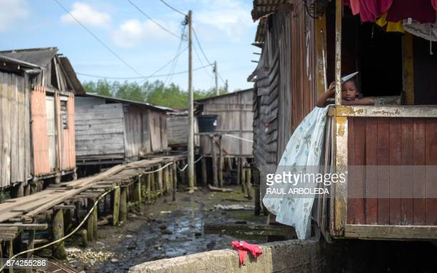 A child stands in a house in City 2000 a shantytown that is home to people displaced by turf wars between criminal gangs in Tumaco municipality...
