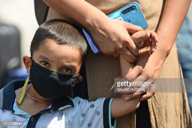 A child stands in a queue while holding hands of his mother outside the entrance of railway station in New Delhi on May 12 2020 India's enormous...