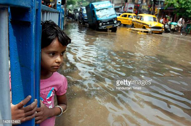 A child stands in flood waters due to heavy rain on Amherst Street on April 6 2012 in Kolkata India The MET department predicts more rainfall through...