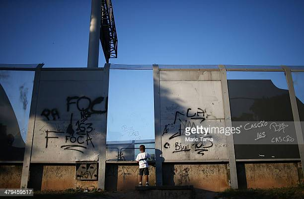 A child stands in front of a divider between the unpacified Complexo da Mare slum complex one of the largest favela complexes in Rio and a main...