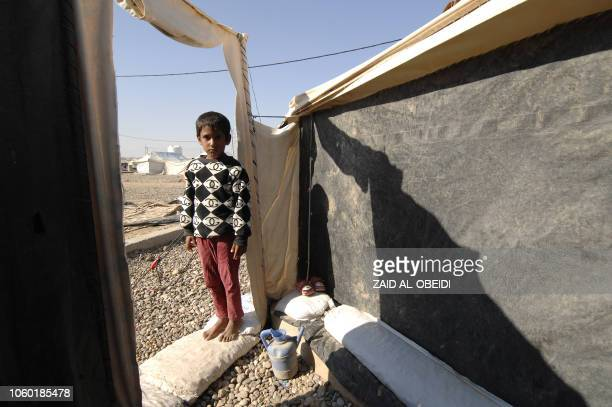 A child stands in front of a tent in a United Nations High Commissioner for Refugees camp for displaced people in Hammam alAlil on the outskirts of...