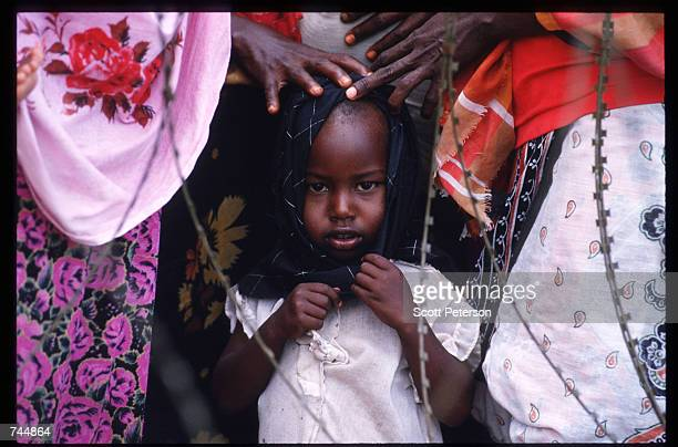 A child stands in line at a food distribution site June 20 1993 in Mogadishu Somalia An estimated 350000 Somalis died due to war famine and disease...