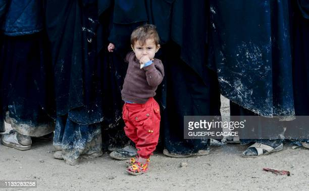 TOPSHOT A child stands in queue in alHol camp which houses relatives of Islamic State group members in alHasakeh governorate in northeastern Syria on...