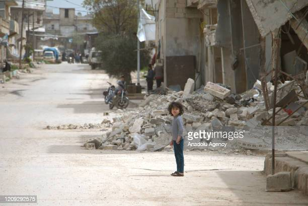 Child stands near debris and damaged buildings as civilians started to return home after the ceasefire on March 06 in Atarib district of Aleppo,...