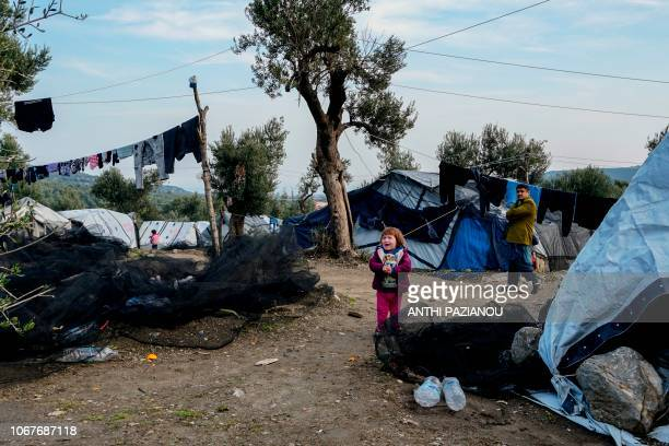 Child stands next a tent at a makeshift camp adjacent to the Moria camp for refugees and migrants on the island of Lesbos, on December 2, 2018. - The...