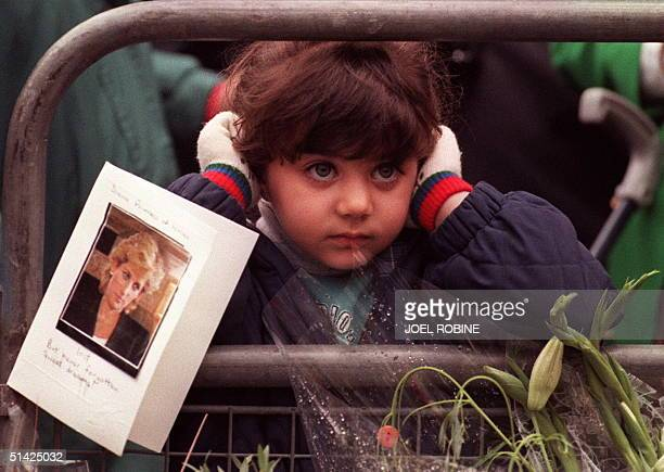 A child stands next to a picture of Diana Princess of Wales 05 September as the crowd waits for the hearse carrying Diana's coffin to leave Saint...