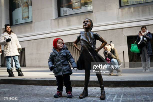 A child stands next to the 'Fearless Girl' after a ceremony to unveil the statue's new location across from the New York Stock Exchange December 10...