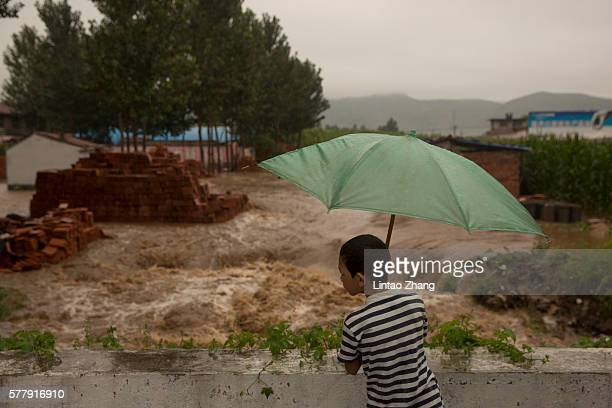 A child stands on a bridge watching flood waters on July 19 2016 at Linzhou Henan Province China Torrential rain has caused severe flooding in...