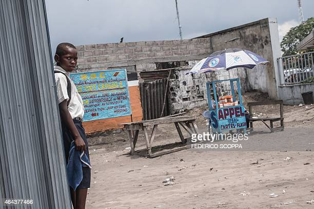 A child stands on February 25 2015 next to a road stall selling cellular telephone cards and internet access in Kinshasa Sales are down and business...
