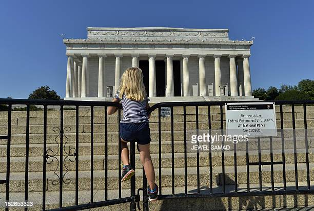 A child stands on the barricade around the Lincoln Memorial in Washington DC on October 2 on the second day of the federal government shutdown US...