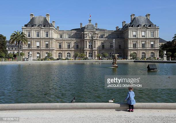 A child stands on the edge of a basin in front of the French Senate which is itself housed in the Luxembourg Palace at the Luxembourg gardens in...