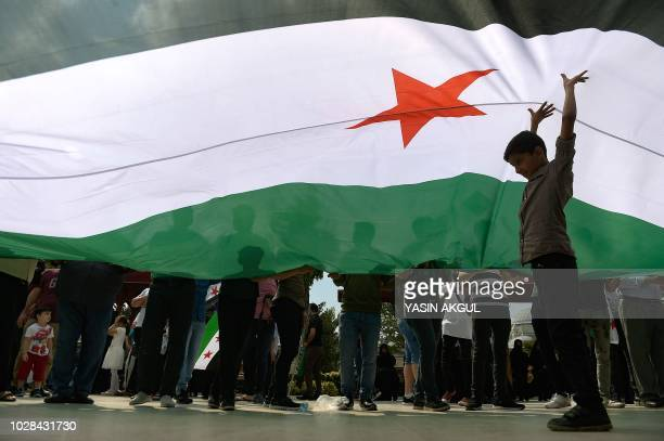 TOPSHOT A child stands under a Free Syrian Army flag during a protest against a Syrian military operation in the rebelheld Idlib province of...