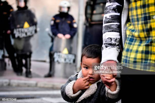 TOPSHOT A child stands with his father in front of offices of the European Union protected by police forces during a demonstration by Greek...