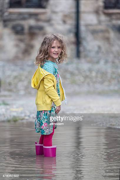 Enfant se dresse avec bottes en caoutchouc dans une flaque