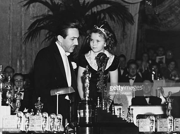 Child star Shirley Temple presents the American animator and producer Walt Disney with an Oscar and seven miniature statuettes for his first feature...