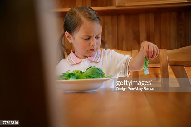 Child stares in disgust at piece of lettuce