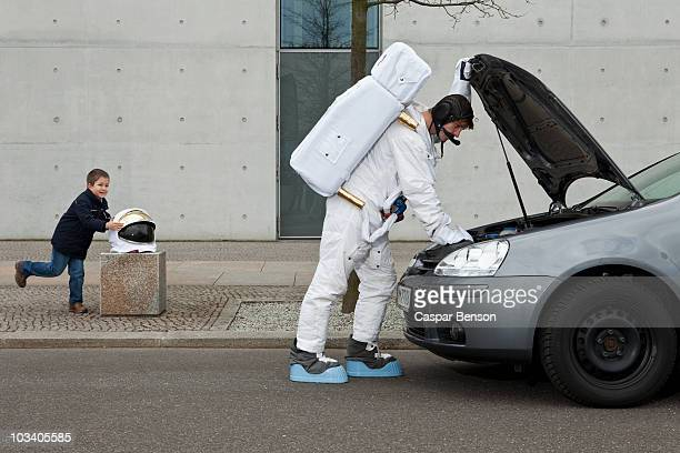 A child stealing a space helmet while an astronaut repairs his broken car