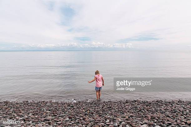 child stepping into cool water on pebbly beach - ポーロック ストックフォトと画像