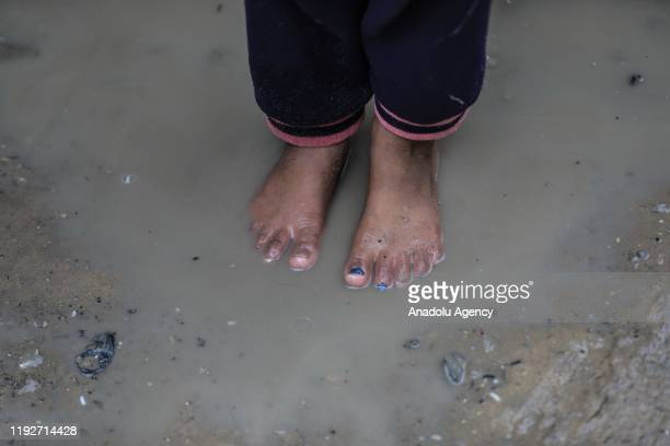 Child steps in a muddy puddle on bare feet following heavy rains in Gaza City, Gaza on January 09, 2020.