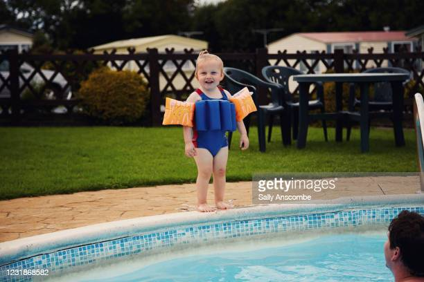 child stood at the edge of the swimming pool - arm band stock pictures, royalty-free photos & images