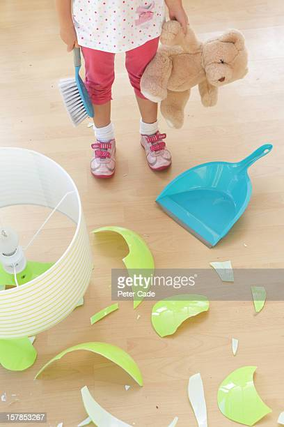 Child stood by broken lamp with dustpan and teddy