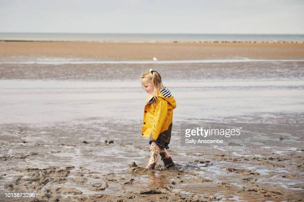 Child stood, stuck in the muddy sinking sand