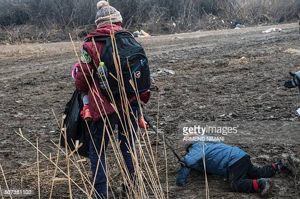 A child strapped with his mother falls as he walks with other migrants and refugees after crossing the Macedonian border into Serbia near the village...