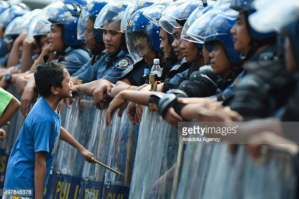 A child strikes a conversation with anti riot police officers as protesters from various groups attempt to march towards the venue of the Asia...