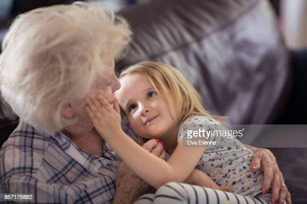 child stroking grandmother's face affectionately - mamie photos et images de collection