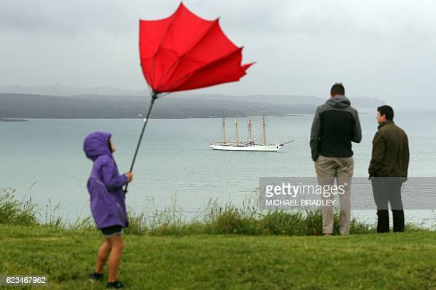 A child struggles with an umbrella as people watch the Bach Esmerelda from Chile arrive into the Waitemata Harbour as part of the fleet entry to...