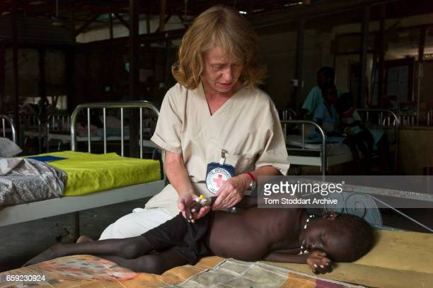 A child suffering from celebral malaria photographed with ICRC nurse Turid Andreassen in the paediatric department of Malakal Teaching Hospital ICRC...