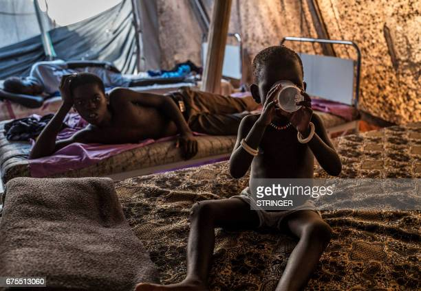 TOPSHOT A child suffering from cholera drinks water at a specialized hospital located near the Mingkaman Internally Displaced People camp on May 1...