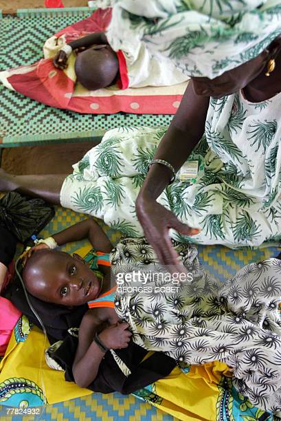 A child suffering from cholera is under intravenous drip as she lies by her mother in a health center in the neighborhood of Ndamatou in Touba 31...